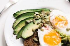 Panino con gli ortaggi freschi, l'avocado, gli uova sode ed i semi di zucca con olio d'oliva e pane Dieta sana o fotografia stock