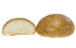 Panino con i semi di sesamo e la metà del panino. Immagini Stock