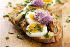 Panino con il adition del pesce dello sgombro, delle uova e dei fiori commestibili della erba cipollina sulla tavola di legno immagini stock libere da diritti