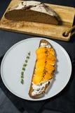 Panino con il cachi e formaggio a pasta molle su un fondo nero fotografia stock