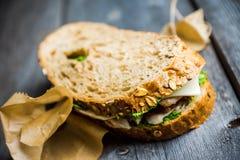 Panino con il pane, il pollo, il pesto ed il formaggio del cereale sui precedenti di legno rustici Fotografia Stock