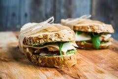 Panino con il pane, il pollo, il pesto ed il formaggio del cereale sui precedenti di legno rustici Fotografia Stock Libera da Diritti