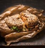 Panino con il pollo, il formaggio e la lattuga in una carta sgualcita su fondo di legno rustico fotografia stock