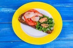 Panino con il pomodoro, i gamberetti, le cozze ed il prezzemolo tagliato sulla a Immagini Stock