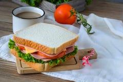 Panino con il prosciutto, formaggio e verdure e caffè caldo sulla tavola di legno Fotografia Stock Libera da Diritti