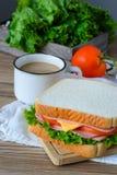 Panino con il prosciutto, formaggio e verdure e caffè caldo sulla tavola di legno Fotografia Stock