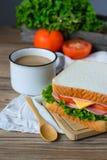 Panino con il prosciutto, formaggio e verdure e caffè sulla tavola di legno Fotografia Stock Libera da Diritti