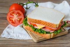 Panino con il prosciutto, il formaggio e le verdure sulla tavola di legno Fotografie Stock Libere da Diritti