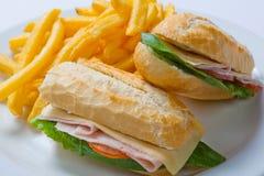Panino con il prosciutto, il pomodoro, il formaggio e le patatine fritte dorate Immagini Stock
