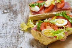 Panino con il prosciutto, l'insalata, le uova ed il pomodoro Fotografia Stock