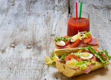 Panino con il prosciutto, l'insalata, le uova ed il pomodoro Fotografie Stock