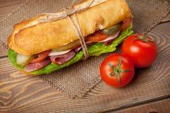 Panino con insalata, il prosciutto, il formaggio ed i pomodori Immagine Stock