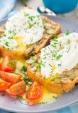 Panino con l'uovo affogato ed i pomodori ciliegia Fotografie Stock Libere da Diritti