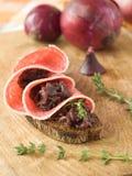 Panino con la salsiccia e la caramella delle cipolle Fotografia Stock
