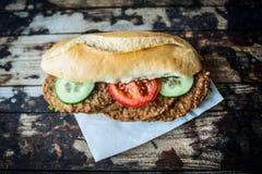 Panino con le cotolette della carne con il cetriolo ed i pomodori su un fondo di legno, vista superiore, tonificante fotografia stock