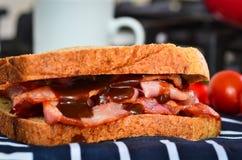 Panino del bacon con salsa marrone Fotografie Stock