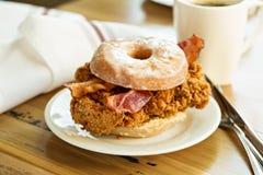 Panino del bacon e del pollo fritto in una ciambella immagini stock