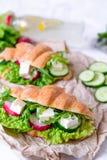 Panino del croissant con formaggio e le verdure per lo spuntino, la carta del mestiere ed il fondo sani di verdi Alimento di esta Immagine Stock
