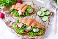 Panino del croissant con formaggio e le verdure per lo spuntino, la carta del mestiere ed il fondo sani di verdi Alimento di esta Fotografia Stock Libera da Diritti