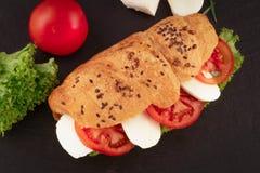 Panino del croissant con la mozzarella ed il pomodoro della lattuga sopra fondo di pietra nero Spuntino sano Vista superiore immagini stock libere da diritti