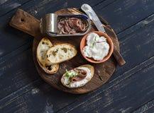 Panino del formaggio di capra e dell'acciuga sul bordo di legno rustico Immagini Stock