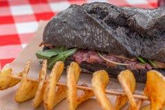 Panino del pane nero con il pomodoro e le patate Immagine Stock