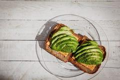 Panino dell'avocado con le erbe, il formaggio ed il pane tostato sui precedenti bianchi di legno immagine stock
