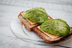 Panino dell'avocado con le erbe, il formaggio ed il pane tostato sui precedenti di legno immagine stock