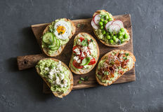 Panino dell'avocado della prima colazione - con bacon croccante, uovo di quaglia, pomodori, formaggio di capra, piselli, ravanell immagini stock