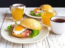 Panino dell'hamburger, tazza di tè e succo d'arancia per la prima colazione Fotografie Stock Libere da Diritti