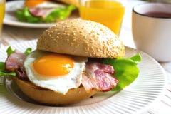Panino dell'hamburger, tazza di tè e succo d'arancia per la prima colazione Immagini Stock Libere da Diritti