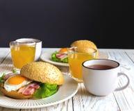 Panino dell'hamburger, tazza di tè e succo d'arancia per la prima colazione Fotografia Stock