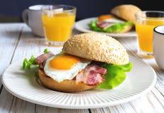 Panino dell'hamburger, tazza di tè e succo d'arancia per la prima colazione Immagini Stock