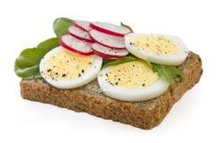 Panino dell'uovo del pane del grano intero isolato su bianco Immagine Stock