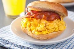 Panino della prima colazione sul bagel con il formaggio del bacon dell'uovo fotografie stock