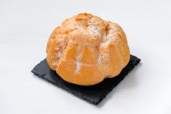 Panino dolce con crema sui piatti di uno scisto e sul fondo di legno fotografie stock