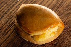 Panino dolce con formaggio, succoso, su un fondo della quercia marrone fotografia stock libera da diritti