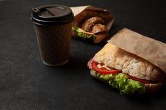 Panino e tazza di caffè su fondo nero Prima colazione o spuntino di mattina una volta affamato Alimento della via da andare immagini stock