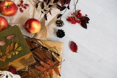 Panino fresco della pasticceria, tazza di caffè caldo e foglie di autunno su fondo di legno Parola di legno AUTUNNO delle lettere Immagine Stock
