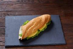 Panino fresco e saporito con formaggio e le verdure sul tagliere sopra fondo di legno, fuoco selettivo Immagini Stock Libere da Diritti