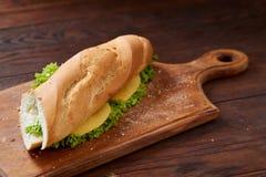 Panino fresco e saporito con formaggio e le verdure sul tagliere sopra fondo di legno, fuoco selettivo Fotografia Stock