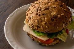 Panino leggero con il pomodoro ed il formaggio in un pane misto dei semi Fotografie Stock