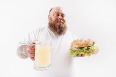 Panino mangiatore di uomini grasso felice con la bevanda dell'alcool Immagini Stock