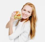 Panino non sano saporito dell'hamburger nella donna affamata delle mani che ottiene con riferimento a Fotografia Stock Libera da Diritti