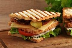 Panino a più strati con formaggio, il prosciutto, i pomodori, i sottaceti ed il le immagini stock