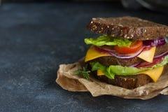 Panino saporito fatto di pane, dei pomodori, della salsiccia, della cipolla e della lattuga sui precedenti scuri, fuoco selettivo Fotografia Stock