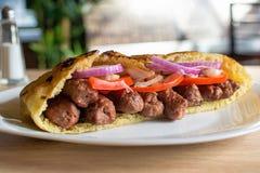 Panino serbo delizioso di kebab del manzo in pane della pita con gli ingredienti freschi dell'insalata Fotografia Stock