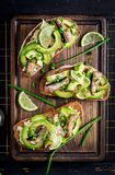 _panino - smorrebrod con spratto, avocado e cremoso formaggio di legno bordo fotografie stock