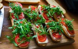Panino sottomarino fresco delle baguette con il prosciutto, il formaggio, i pomodori ed il razzo selvaggio Fuoco selettivo immagine stock libera da diritti