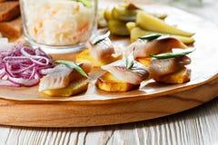 Panino sulle patate fritte con l'aringa, cipolla verde Aperitivo saporito con i crauti, cetriolo marinato, senape sopra immagine stock libera da diritti